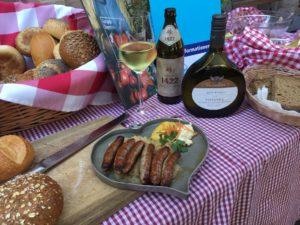 Bratwurst umrundet von Wein und Bier
